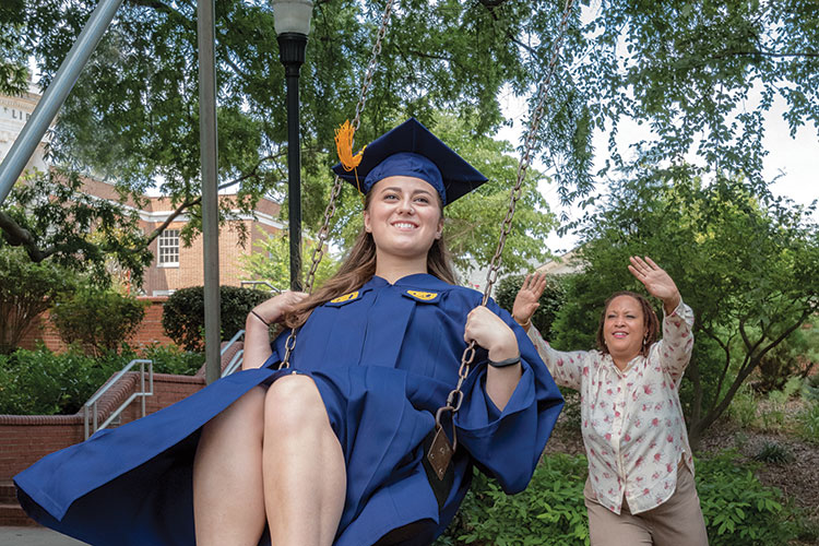 photo of woman pushing UNCG student dressed in cap and gown on the swing near the student center