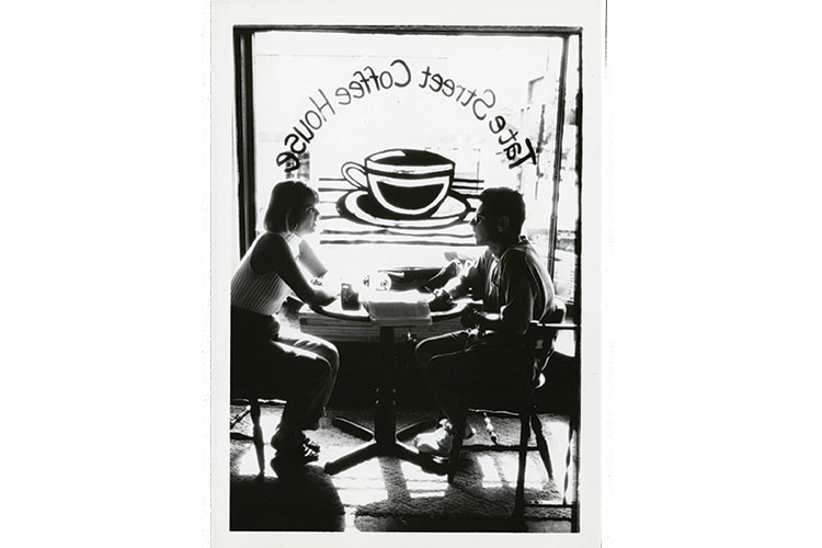 photo from inside the Tate Street Coffee House, showing two people seated at a table in front of the window